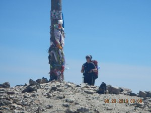 Sue leaving her stone at the top of the rockpile. Notice the hats, ribbons, notes that peregrinos have left stapled to the pole